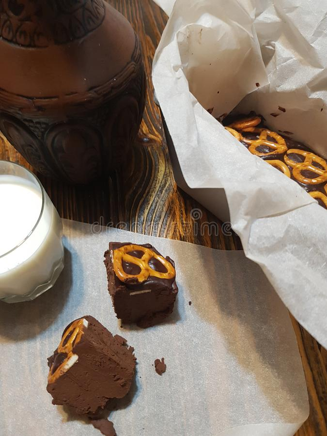 Eigengemaakt chocoladedessert in kraftpapier-document op een houten lijst met een glas melk en een klei jugand stock afbeeldingen