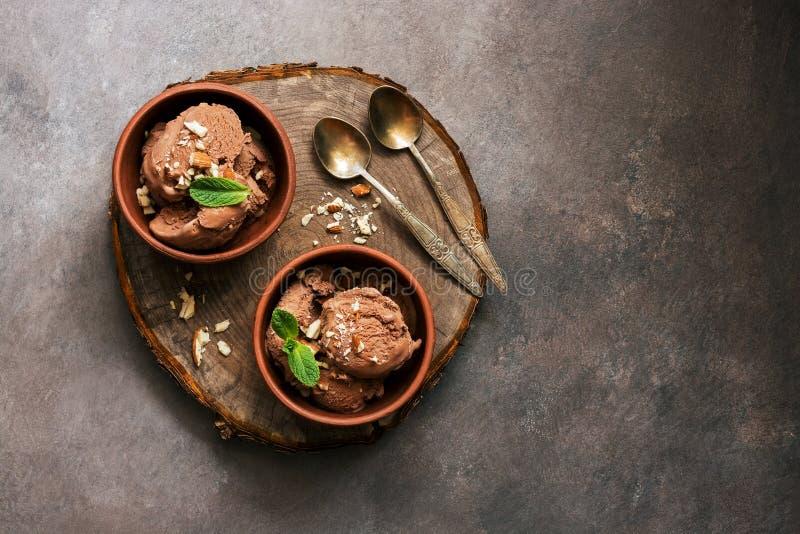 Eigengemaakt chocoladeroomijs met munt en noten in kommen op een stomp scherpe raad, donkere rustieke achtergrond Luchtmening, ex stock fotografie