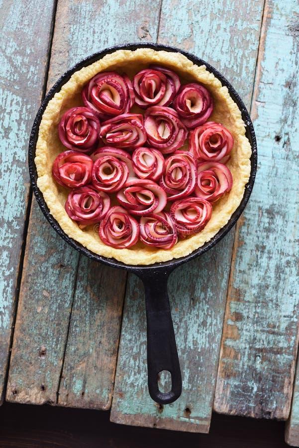 Eigengemaakt gebakje Open pastei met appelrozen in gietijzerpan op s royalty-vrije stock foto