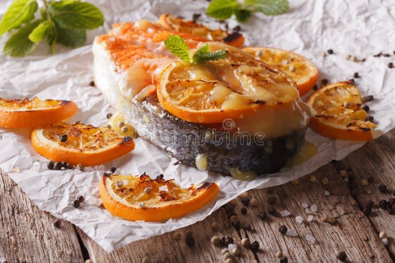 Eigengemaakt gebakken zalmlapje vlees met sinaasappelen op bakseldocument horizo royalty-vrije stock fotografie