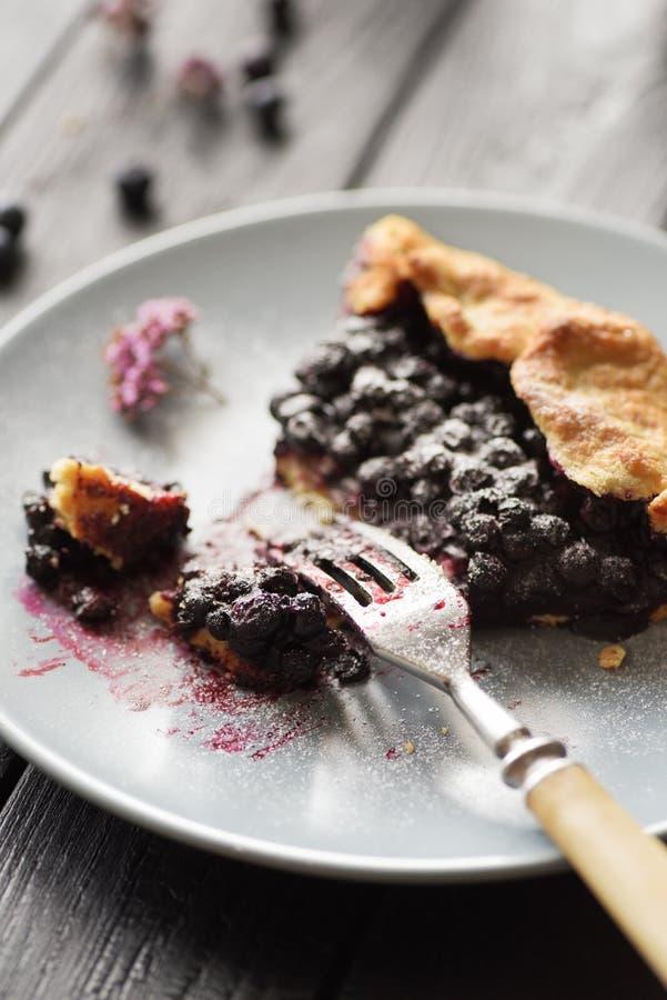 Eigengemaakt gezond dessert Stuk van heerlijke bosbessengalette in grijze plaat op donkere achtergrond stock foto's