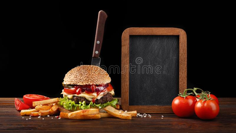 Eigengemaakt hamburgerclose-up met rundvlees, tomaat, sla, kaas, frieten en schoolbord op houten lijst In de geplakte hamburger stock fotografie