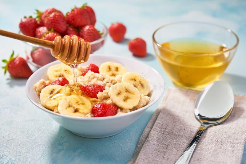 Eigengemaakt havermeel met verse bessen en honing voor ontbijt op een turkooise achtergrond Heerlijk en gezond voedsel voor ontbi royalty-vrije stock foto's