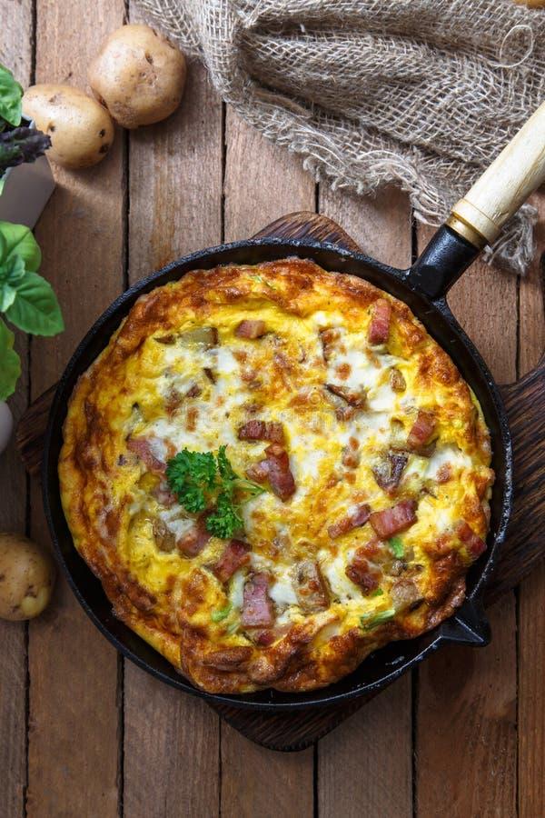 Eigengemaakt ontbijt met heerlijke die omelet met ham, aardappel en kaas, hoogste mening wordt ingediend stock fotografie