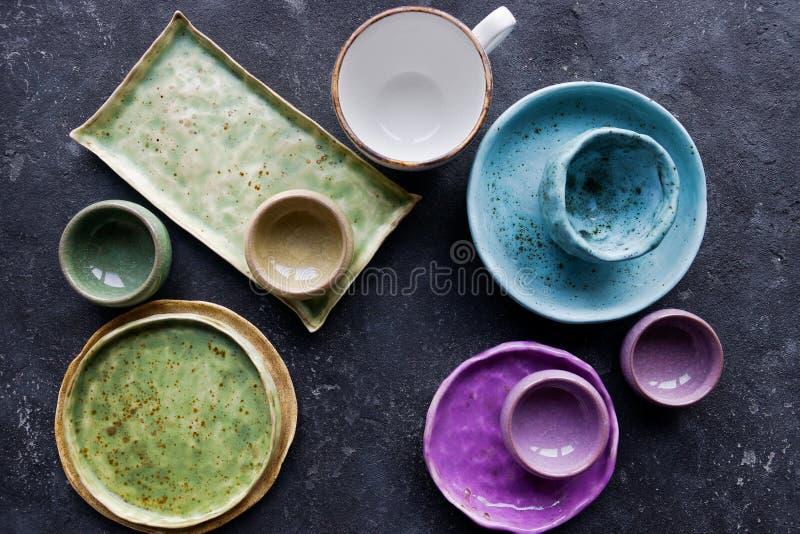 Eigengemaakt rustiek aardewerk, kleurrijke platen en kommen op donkere steen concrete achtergrond royalty-vrije stock foto