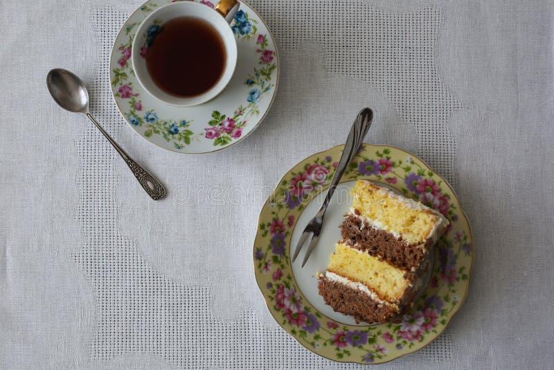 Eigengemaakt stuk van biscuitgebak met vanille en cacaolagen De oude uitstekende kop met bloemen en de kleine theelepel bevinden  royalty-vrije stock foto's