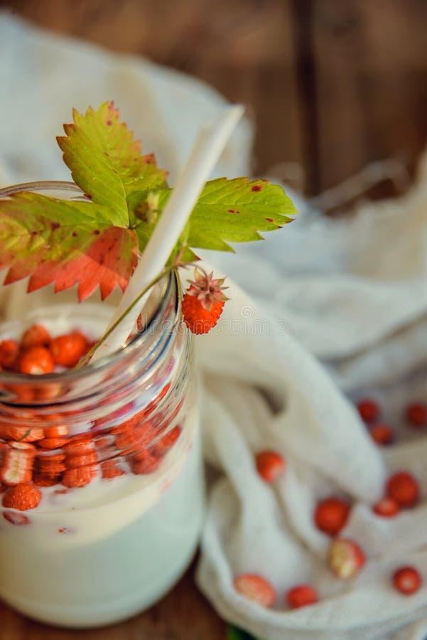 Eigengemaakte aardbeiyoghurt met verse wilde aardbeien en munt in een kruik op een houten raad, selectieve nadruk stock foto's