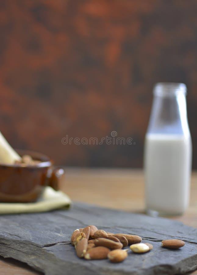 Eigengemaakte Amandelmelk in fles met amandelen in een kom Zuivel alternatieve melk stock foto's