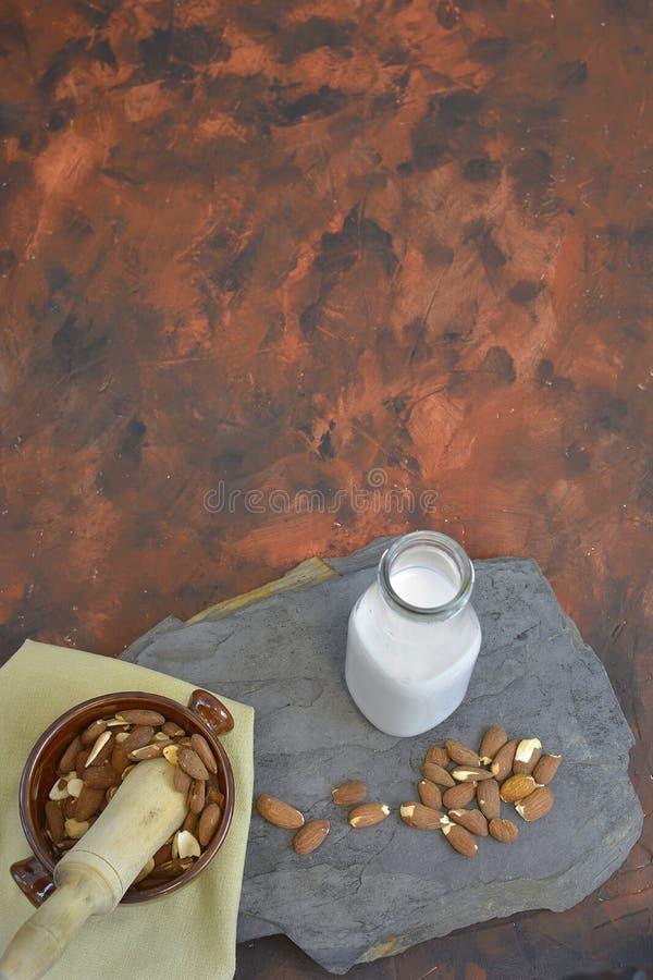 Eigengemaakte Amandelmelk in fles met amandelen in een kom Zuivel alternatieve melk stock fotografie