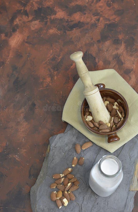 Eigengemaakte Amandelmelk in fles met amandelen in een kom Zuivel alternatieve melk royalty-vrije stock afbeelding