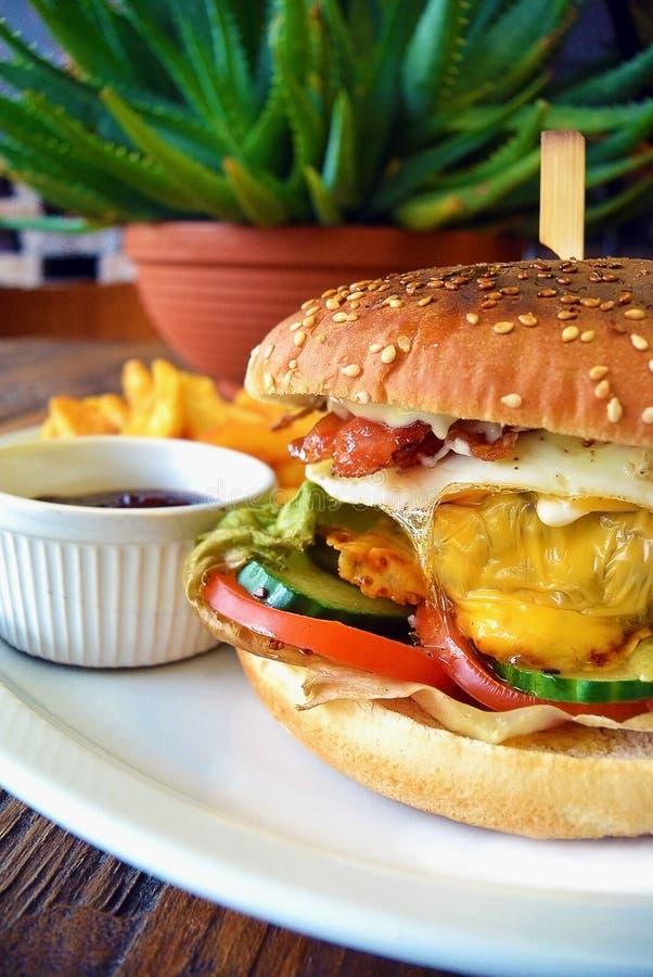 Eigengemaakte Baconhamburger met Eikaas en groenten stock afbeeldingen