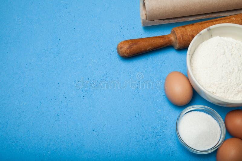 Eigengemaakte bakselachtergrond met cakeingrediënten op blauwe lijst stock afbeelding