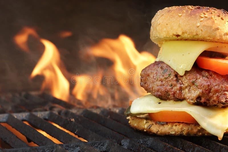 Eigengemaakte BBQ Rundvleeshamburger op de Hete Vlammende Grill stock foto