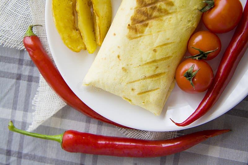 Eigengemaakte burrito en gebraden die aardappel met tomaat en Spaanse peper wordt gediend royalty-vrije stock afbeelding