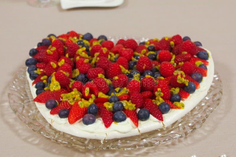 Eigengemaakte cake met Aardbeien en bosbessen voor Valentine& x27; s Daghart op een tafelkleed dat van de glasplaat wordt gevormd royalty-vrije stock foto
