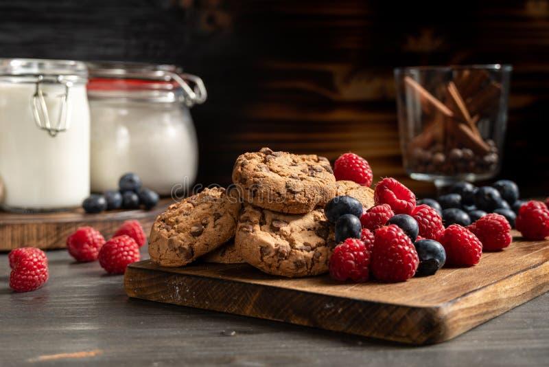Eigengemaakte chocoladekoekjes en eetbare bessen over schotel stock foto