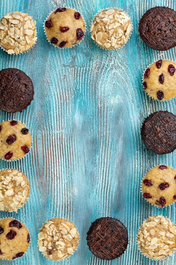 Eigengemaakte chocoladeschilfermuffins als kader op blauwe houten lijst stock afbeeldingen