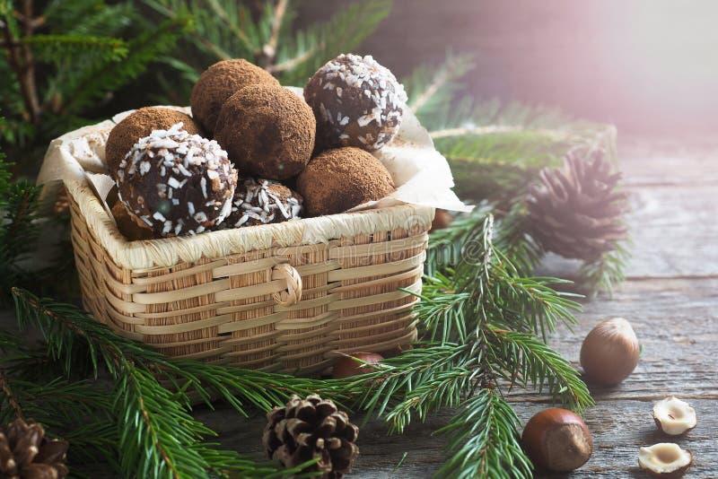 Eigengemaakte chocoladetruffels met cacao en kokosnoot in een doos Kerstmistak en klokken royalty-vrije stock fotografie