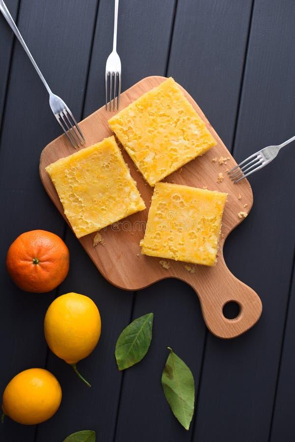 Eigengemaakte citroenpastei met verse citrusvruchten op donkere hoogste mening als achtergrond stock afbeeldingen