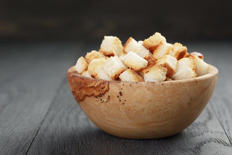 Eigengemaakte croutons van wit brood in houten kom stock afbeelding