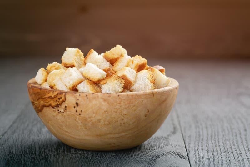 Eigengemaakte croutons van wit brood in houten kom op eiken lijst stock fotografie