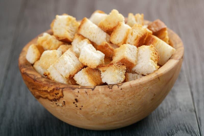 Eigengemaakte croutons van wit brood in houten kom op eiken lijst stock foto