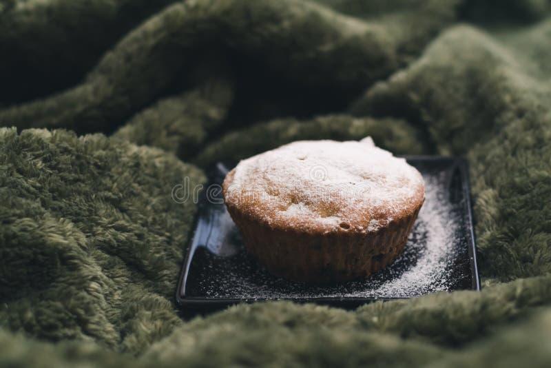 Eigengemaakte cupcake met gepoederde suiker op een zwarte plaat op een achtergrond van groene textiel Het concept een comfortabel royalty-vrije stock afbeelding