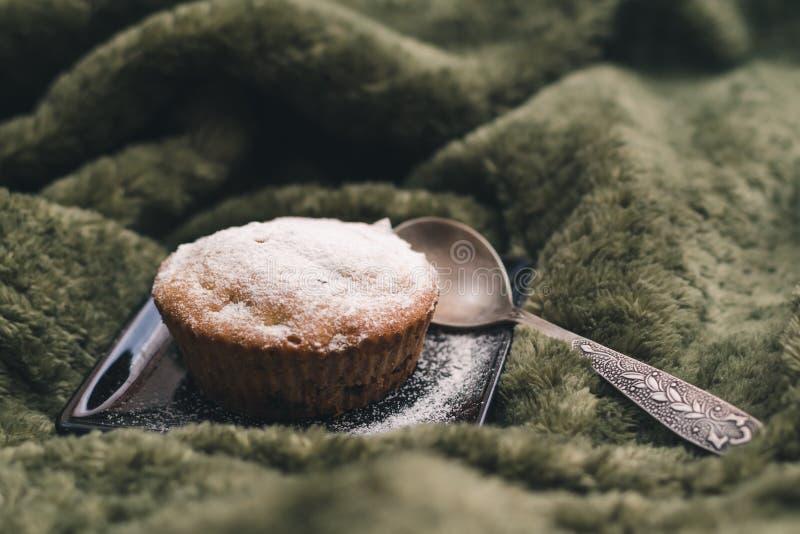 Eigengemaakte cupcake met gepoederde suiker op een zwarte plaat en een theelepeltje stock afbeelding