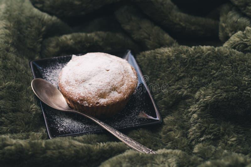 Eigengemaakte cupcake met gepoederde suiker op een zwarte plaat en een theelepeltje op een achtergrond van groene textiel stock afbeeldingen