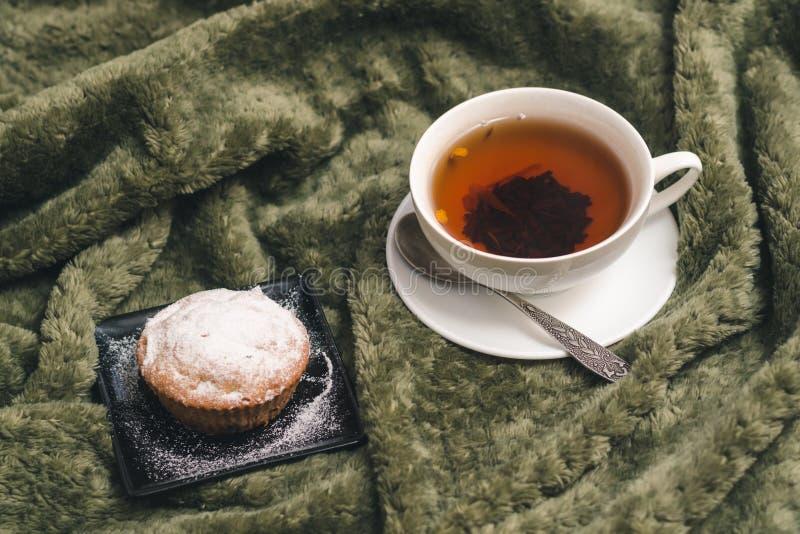 Eigengemaakte cupcake met gepoederde suiker op een zwarte plaat en een witte kop thee met natuurlijke additieven stock afbeeldingen
