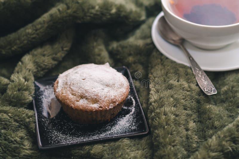 Eigengemaakte cupcake met gepoederde suiker op een zwarte plaat en een witte kop thee met natuurlijke additieven royalty-vrije stock foto