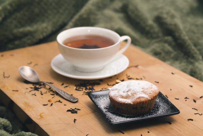 Eigengemaakte cupcake met gepoederde suiker op een zwarte plaat en een witte kop thee met natuurlijke additieven op een houten di stock foto