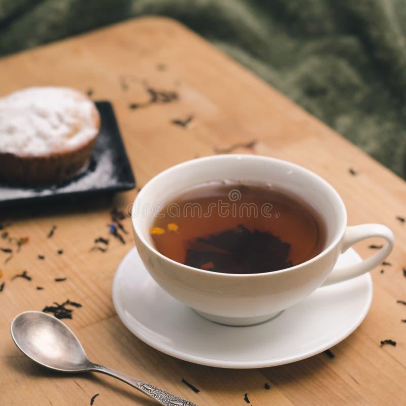 Eigengemaakte cupcake met gepoederde suiker op een zwarte plaat en een witte kop thee met natuurlijke additieven op een houten di royalty-vrije stock afbeelding