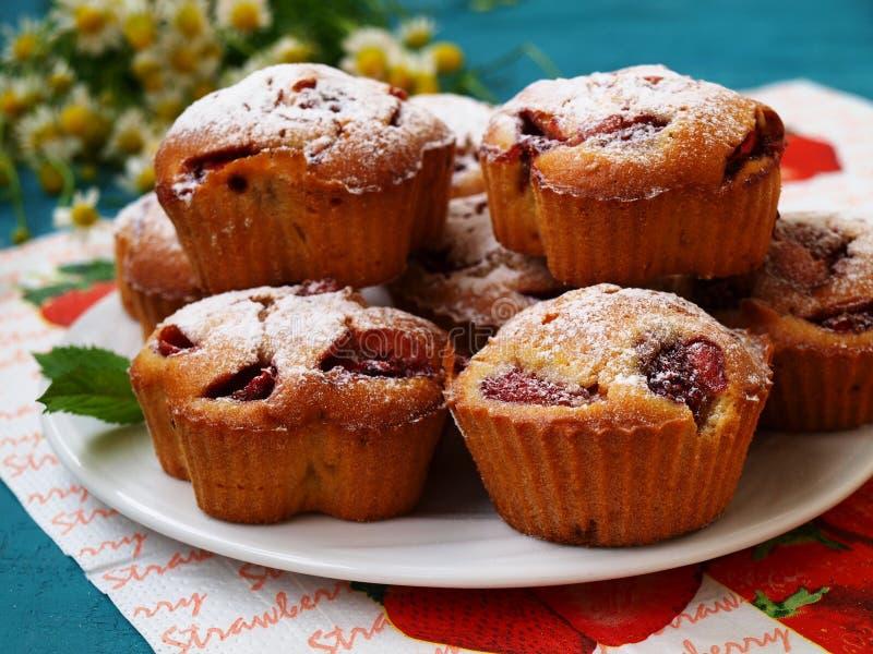 Eigengemaakte cupcakes met aardbeien op een witte plaat royalty-vrije stock afbeeldingen