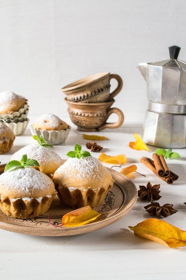 Eigengemaakte cupcakes met gepoederde suiker met pijpjes kaneel, anijsplantsterren, en de herfstbladeren op witte houten lijst stock afbeelding