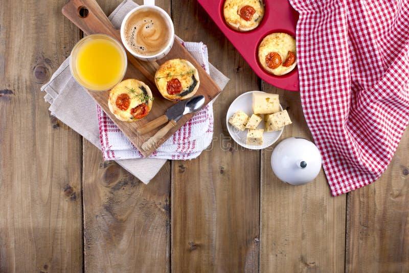 Eigengemaakte cupcakes met kaas en kersentomaten op een houten raad, een lepel en een mes lijsthanddoek in een rode kooi, een gla stock fotografie