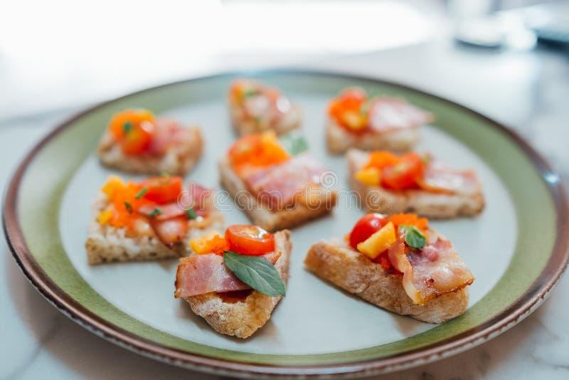 Eigengemaakte die canapes met bacontomaat en vissenkuiten wordt bedekt royalty-vrije stock foto's