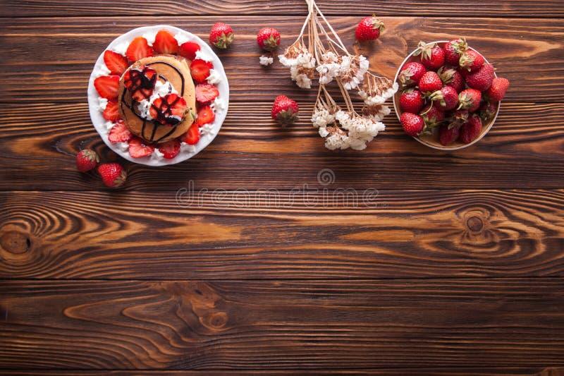 Eigengemaakte die pannekoeken met aardbeien, slagroom en chocoladebovenste laagje, met bloemen op houten achtergrond wordt verfra stock afbeelding