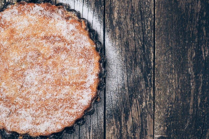 Eigengemaakte die pastei met gepoederde suiker op rustieke houten achtergrond wordt bestrooid Ruimte voor tekst stock afbeelding