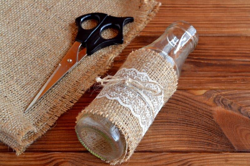 Eigengemaakte diy glasfles Schaar, jute, met de hand gemaakte vaas op een houten lijst stock fotografie