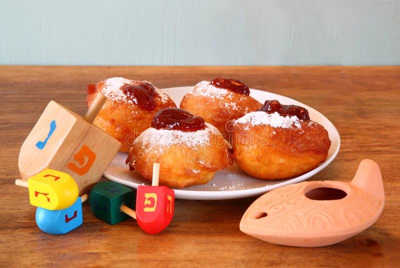Eigengemaakte donuts en houten dreidels (tol) voor hanukkah Joodse vakantie over houten lijst royalty-vrije stock foto's