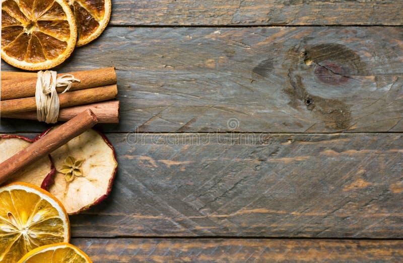 Eigengemaakte droge vruchten plakken van oranje appelpijpjes kaneel op oude plank houten achtergrond De decoratie van nieuwjaarke stock afbeeldingen