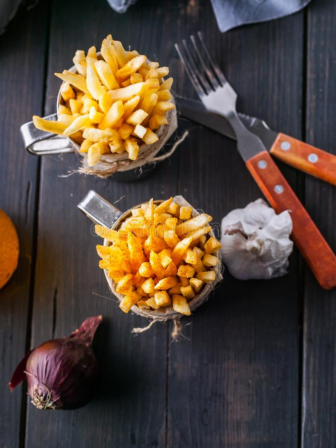 Eigengemaakte Frieten, Ui, Knoflook, Vork en Lepel op Donkere Houten Lijst Verticaal schot stock foto's
