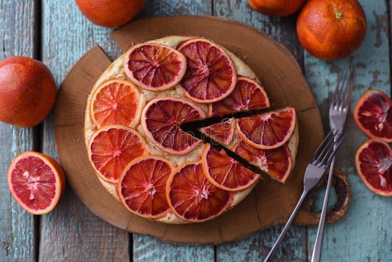 Eigengemaakte fruitcake De ronde die cake van de bloedsinaasappel op eiken raad wordt gesneden royalty-vrije stock foto