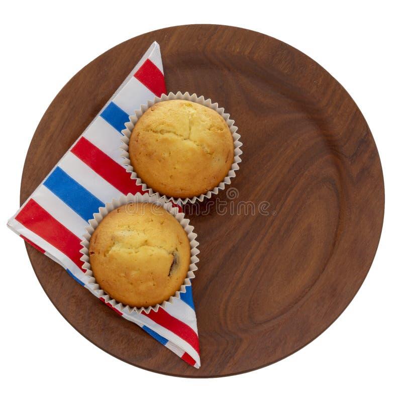 Eigengemaakte fruitmuffins, cupcakes op rood wit en blauw die servet, servet op plaat, op wit wordt geïsoleerd Klein huis twee stock afbeeldingen
