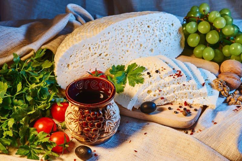 eigengemaakte Georgische Imeretian-kaas op een houten Raad, kersentomaten, okkernoten, druiven, kruiden royalty-vrije stock foto