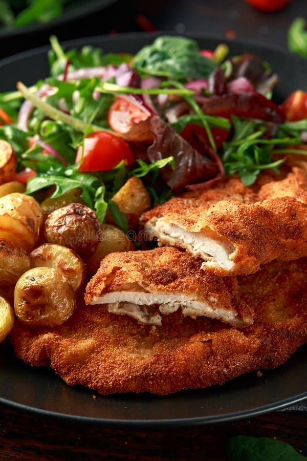 Eigengemaakte gepaneerde varkensvleesschnitzel met braadstukaardappel en groenten stock afbeeldingen