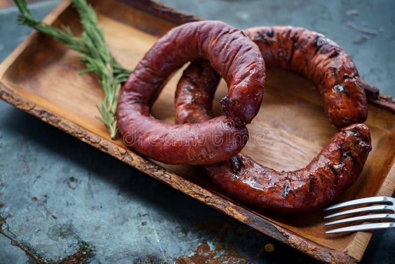 Eigengemaakte gerookte Duitse ronde worst op houten plaat stock afbeelding