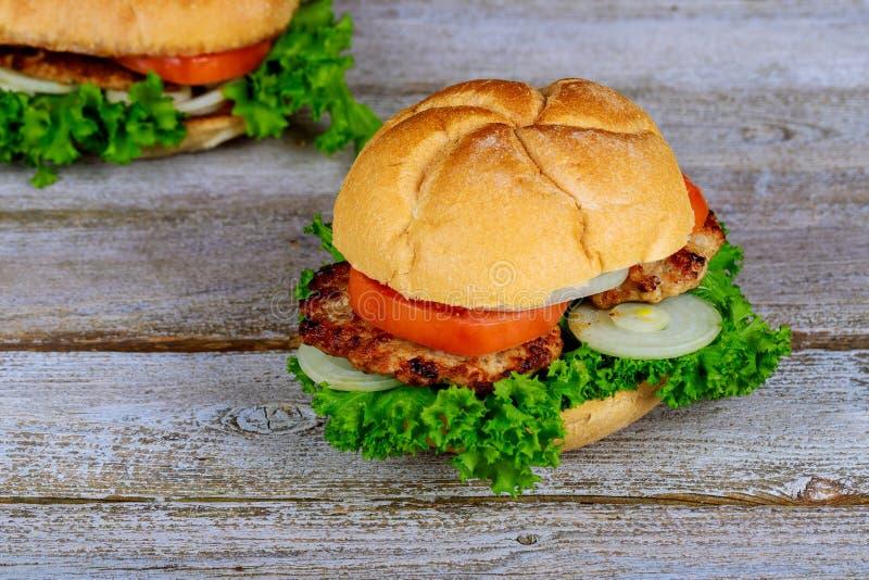 Eigengemaakte geroosterde hamburger twee met rundvlees, ui, tomaat, sla en kaas royalty-vrije stock foto's