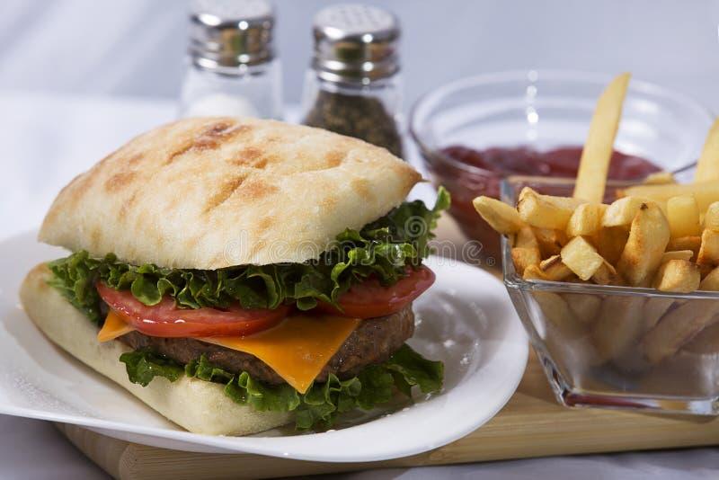 Eigengemaakte Gezonde Cheeseburger op Ciabatta-Broodje, met Frieten royalty-vrije stock afbeelding
